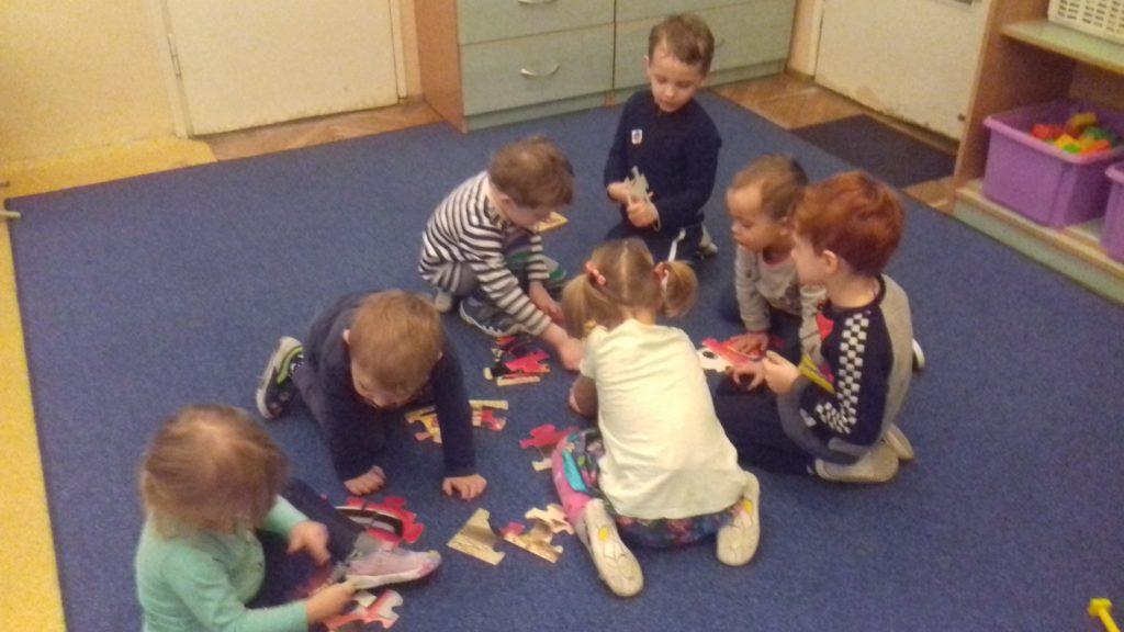 Grupa dzieci układa puzzle na dywanie