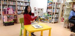 Pani bibliotekarka siedzi przy małym stoliku na tle książek. Trzyma w uniesionych rękach otwartą książkę