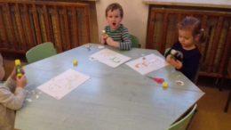 Dzieci przy stoliku wykonują bałwanki na kartkach