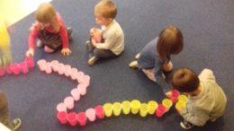 Dzieci tworzą bardzo długi rząd kolorowych kubeczków