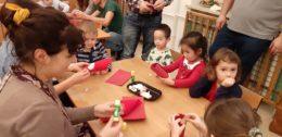 Dzieci wraz z rodzicami siedzą przy stole, na którym leżą kleje i czerwone papiery. Wykonują z nich Mikołaja