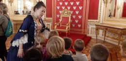 Dzieci stoją na tle tronu królewskiego. Przed nimi w pani przewodnik ubrana w starodawną suknię balową wskazuje na tron
