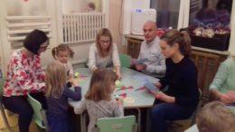 Rodzice wraz z dziećmi siedzą przy stoliku i wykonują papierowy łańcuch świąteczny