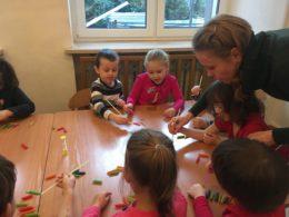 Dzieci siedzą przy stoliku bawiąc się kolorowym makaronem