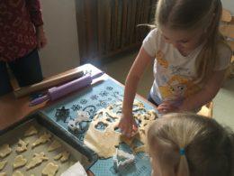 Na stole leży rozwałkowane ciasto. Dzieci odciskają formę ciasteczek
