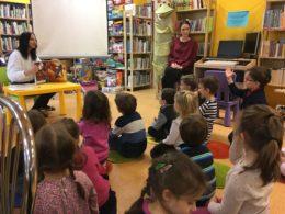 Dzieci siedzą na podłodze na kolorowych dywanikach zwrócone do pani bibliotekarki, która trzyma w ręku książkę