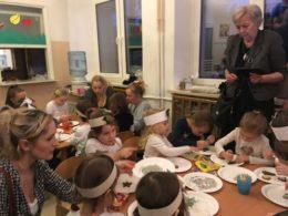 Rodzice wraz z dziećmi siedzą przy stolikach, na których na papierowych talerzykach leżą pierniczki. Dzieci ozdabiają je wraz z rodzicami. Przedszkolaki mają na głowach opaski śnieżynek