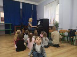 dzieci siedzą na podłodze słuchając jak pani od rytmiki gra na pianinie