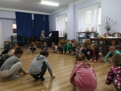 dzieci w kole kucają, wystukując rytm o podłogę