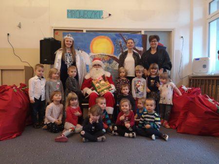 Dzieci pozują do zdjęcia z Mikołajem, Panią Śnieżynką i Panią Dyrektor
