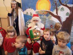 Dzieci pozują do zdjęcia z Mikołajem i Panią Śnieżynką na tle zimowego krajobrazu