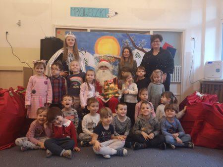 Dzieci pozują do zdjęcia z Mikołajem, Panią Śnieżynką na tle dekoracji zimowej