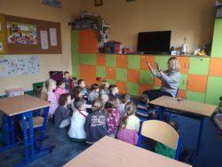 Dzieci siedzą na dywanie z tyłu sali szkolnej. Przed nimi nauczycielka z podniesionymi rękami coś im tłumaczy. W tle widać szafki szkolne
