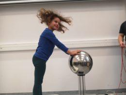 Dziewczynka dotyka oburącz srebrnej kuli, która jest naelektryzowana. Przechodzący przez nią prąd unosi włosy dziewczynki
