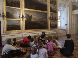 Dzieci siedzą na podłodze w jednej z sal Zamku Pod Blachą. W tle widać obraz na całej ścianie. Pani przewodnik siedzi przed dziećmi i opowiada im o widocznych obrazach