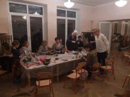 Przy złączonych stołach rodzice wykonują ozdoby choinkowe