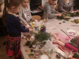 Dwie dziewczynki przy stole pokrytym materiałami do wykonania stroików ozdabiają swoje ozdoby świąteczne