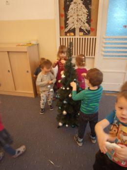 Dzieci ubierają na dywanie małą choinkę