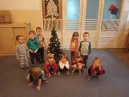 Dzieci pozują do zdjęcia na tle małej choinki
