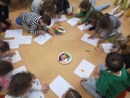 Dzieci rysują na kartkach na podłodze biblioteki
