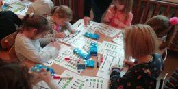 dzieci siedzą przy stolikach i rysują trasy dla ozobotów