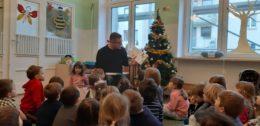 Na tle choinki siedzi tata Leopolda. W ręku trzyma książkę, którą pokazuje dzieciom