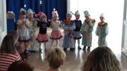 Maluchy stoją w szeregu przebrane za krasnale. Pokazują ruchem tekst piosenki. Na widowni siedzą rodzice