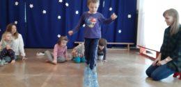 Na sali rytmiczne dzieci pokonują tor przeszkód. Chłopiec przechodzi przez tor z butelek plastikowych zachowując równowagę. Obok klęczy Pani Kasia uśmiechając się. Inne dzieci z tyłu obserwują chłopca