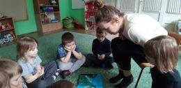 Dzieci siedzą w kole na dywanie. Mama Helenki na krzesełku po środku czyta im książkę