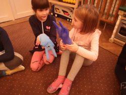 dwie dziewczynki trzymają nadmuchane gumowe rękawiczki, ozdobione jak króliki