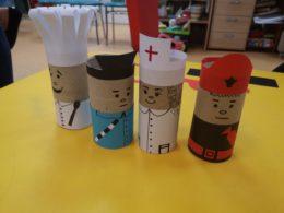 Na stole w bibliotece stoją wykonane z rolek po papierze toaletowym i papieru kolorowego postacie takie jak: pielęgniarz, strażak, kucharz, policjant