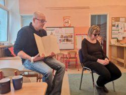 Na krzesełkach siedzą przedstawiciele Fundacji Pomóż Mi Zrobić To Samemu. Mężczyzna trzyma w ręku książkę napisaną alfabetem Braille'a. Obok siedzi niewidoma kobieta, która odpowiada na pytania dzieci