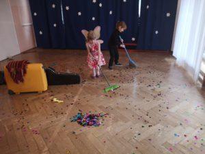 dzieci sprzątają rozsypane konfeti na podłodze