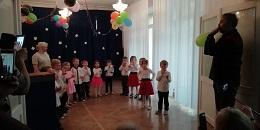Dzieci ubrane na galowo są ustawione w półkole. Na Widowni siedzą rodzice, którzy ich fotografują