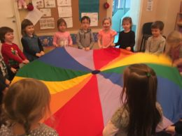 Dzieci stoją w kole trzymając w rekach wielką, rozłożoną, kolorową chustę animacyjną