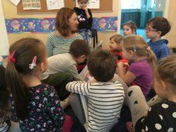 Dzieci otaczają mamę, oglądając książeczkę