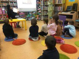 Dzieci siedzą w bibliotece na podłodze na kolorowych dywanikach. Są zwrócone w stronę pani bibliotekarki, która pokazuje im książkę. Za nim są wyświetlane ilustracje na projektorze