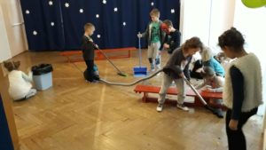 Dzieci odkurzają i sprzątają salę