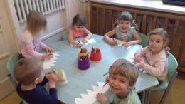 Dzieci siedzą przy stoliku wykonując papierowe korony