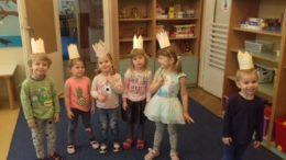 Dzieci stoją w rzędzie z papierowymi koronami na głowie