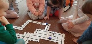 Na dywanie dzieci ułożyły puzzle, które przedstawiają trasę dla ozobotów. Dzieci obserwują ozoboty poruszające się po wykonanej przez nie trasie
