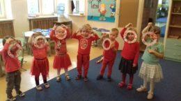 Dzieci ubrane na czerwono pokazują wykonane przez siebie prace