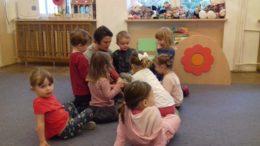 Mama Tytusa siedzi z dziećmi w kole i czyta im bajkę na dywanie w sali