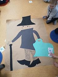 Na podłodze leży papier pakowy, na którym wyklejona jest postać z kolorowego papieru. Jest to Pan Andersen. Ma walizkę, kapelusz i laskę
