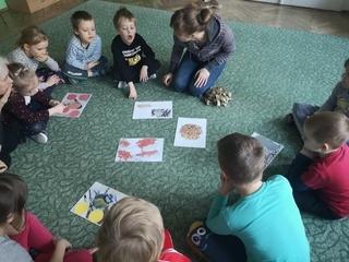 dzieci siedzą w kole na dywanie układając zadania