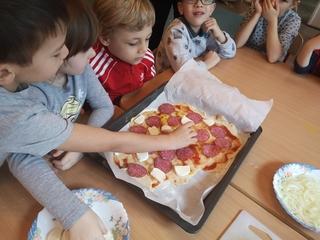 Dzieci siedzą przy stoliku. Przed nimi leży brytfanna z pizzą. Dzieci układają na niej salami, i ser