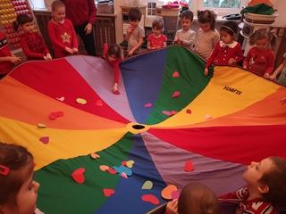 Dzieci są ustawione w kole, trzymają kolorową, duża chustę animacyjną. Na chuście są rozsypane serduszka papierowe