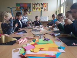 Dzieci siedzą przy stole, na którym leżą kolorowe papiery. Przedszkolaki wycinają, kleją, wykonują lodowe zamki z papieru