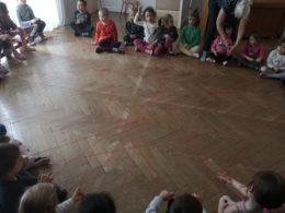 dzieci siedzą w kole na sali rytmicznej tworząc między sobą pajęczynę z wełny