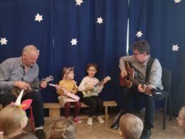 Gucio i Duduś grają na instrumentach, gitarze i ukulele. Między nimi siedzą dwie dziewczynki, które grają na swoich ukulele przyniesionych z domu